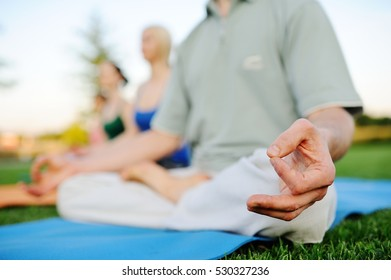 Young man and woman doing yoga on the healing of fresh grass. Healthy lifestyle