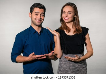 A young man and woman dressed in business casual clothes stand in front of a grey/white background, smiling and looking happy. The woman presents the man to the camera with her hands.