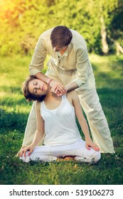 Young man and woman dressed in a white robe doing thai massage with yoga exercises sitting on the grass. Sunny summer park with green lawn in the background