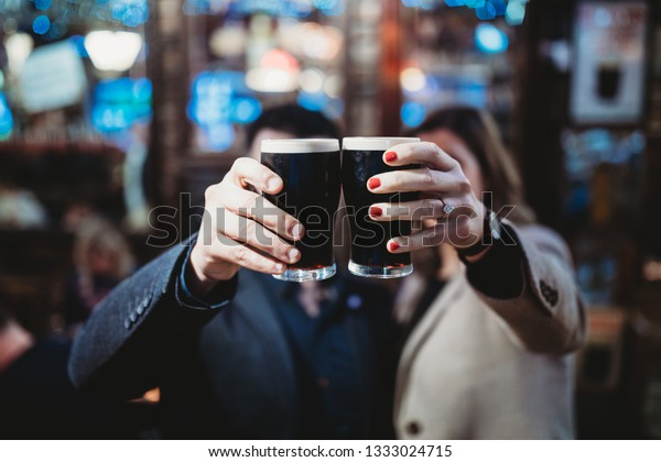 Young Man and Woman drinking Guinness