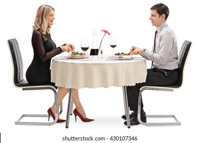 Young man and woman eating on a date seated at a restaurant table isolated on white background