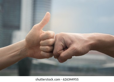 Young man and woman are fist bumping,one fist and one fist raise thumb. after success in plan ,business,feel happy,win in game and promise to do something.