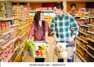 Young man and a woman flirting at the supermarket while they do their shopping