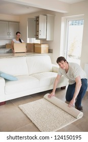 Young man and woman furnishing their kitchen and living room for a relocation