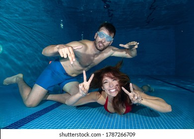 Young man and a young woman goofing around underwater in the swimming pool