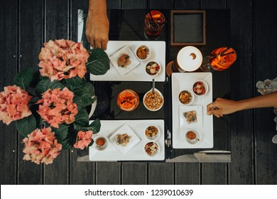 young man and woman hands picking snacks from Italian aperitif with Spritz cocktail, drink with Aperol, Prosecco & soda. Beautiful dark wooden table  with Rose flower decoration top view.