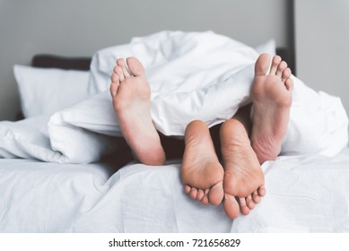 Young man and woman having fun under quilt in bedroom