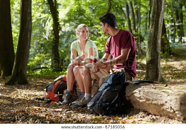 young man and woman having lunch with sandwich during hiking excursion. Horizontal shape, full length