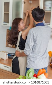 Young man and woman help cook in the kitchen.Husband and wife cook in the kitchen happily