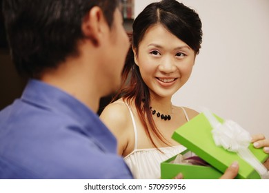 Young man and woman holding gift box, looking at each other