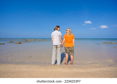 Young man and woman holding hands on island beach during low water
