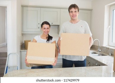 Young man and woman holding moving boxes in kitchen