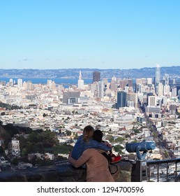 Young man and woman hugging and contemplating the skyline of San Francisco, with Transamerica Pyramid, Salesforce tower and Market street in sight.