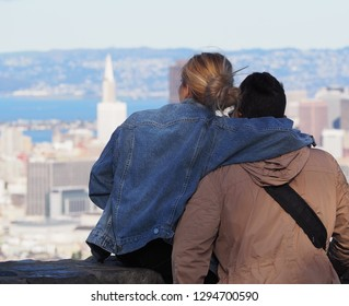 Young man and woman hugging and looking at the city of San Francisco, with the Transamerica Pyramid in background