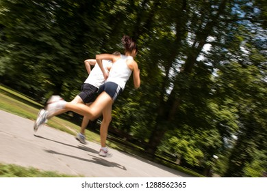 Young man and woman jogging outdoor in nature - motion blur image (panning)