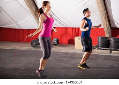 Young man and woman jumping ropes as part of their workout in a gym