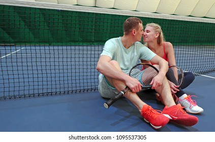young man and woman are kissing while sitting on a tennis court near the tennis net