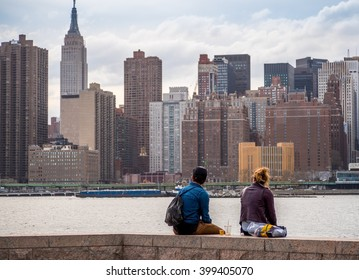 A young man and woman looking at Manhattan skyline in New York City