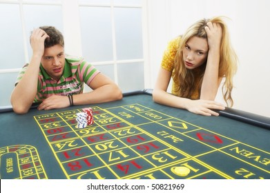 Young man and woman losing on roulette table