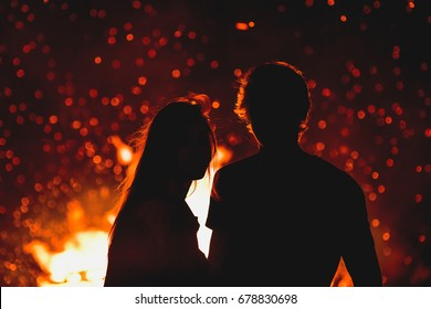Young man and woman in love standing by the big fire - valentine or marriage concept photo