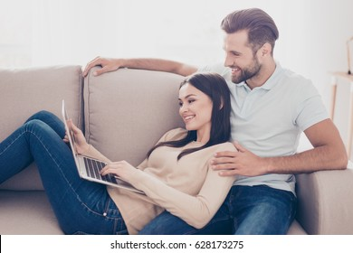 Young man and woman in love are watching film on laptop. They sit on sofa at home, smiling and excited