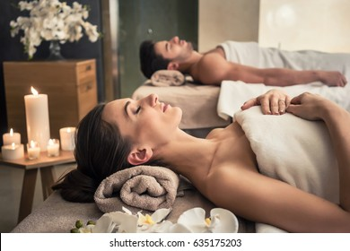 Photo of Young man and woman lying down on massage beds at Asian luxury spa and wellness center
