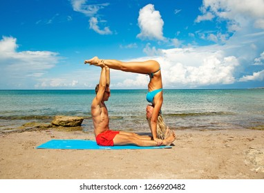 young man and woman on beach doing fitness yoga exercise together. Acroyoga element for strength and balance
