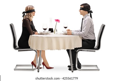 Young man and woman on a blind date seated at a restaurant table isolated on white background