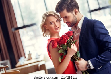 Young man and woman on date in restaurant standing with red roses bouquet lady looking camera smiling happy