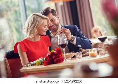 Young man and woman on date in restaurant sitting at table guy holding fork with salad feeding lady smiling playful