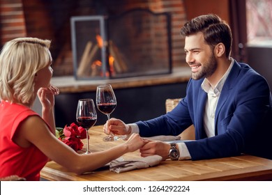 Young man and woman on date in restaurant sitting table holding glasses drinking wine holding hands smiling happy