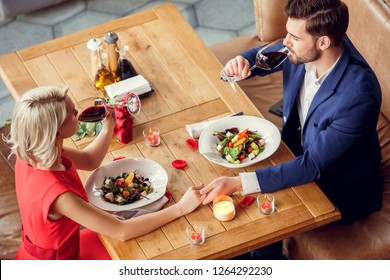 Young man and woman on date in restaurant sitting at table eating vegetable salad holding glasses drinking red wine holding hands top view