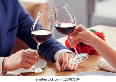 Young man and woman on date in restaurant sitting table holding glasses drinking red wine cheers close-up