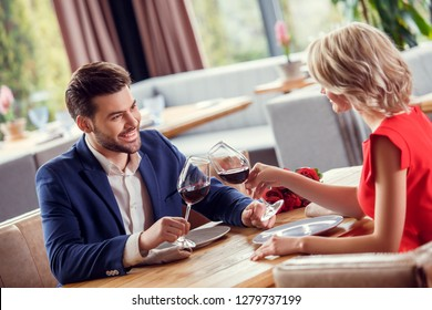Young man and woman on date in restaurant sitting table holding glasses drinking wine toast talking smiling joyful