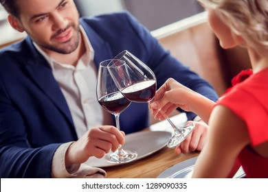 Young man and woman on date in restaurant sitting table holding glasses drinking red wine cheers flirting close-up