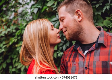 Young man and woman on the nature. Playful couple in love. Woman if red dress. Man in red shirt