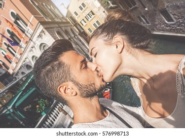 Young man and woman on their romantic trip to Venice - Beautiful couple taking a selfie while kissing on one of the bridges in Venice - Teenagers, holidays and love concept
