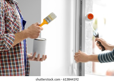 Young man and woman painting window at home