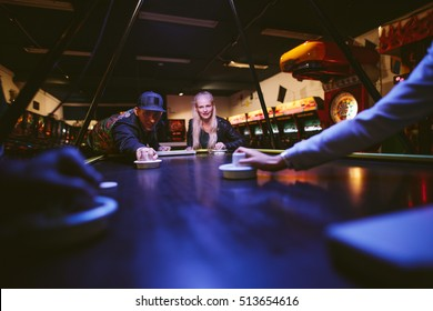Young man and woman playing air hockey game at amusement park. Young people having fun playing table air hockey.