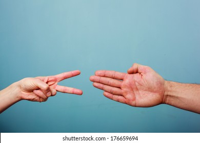 Young man and woman are playing rock paper scissors