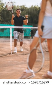 Young man and woman playing tennis at the court