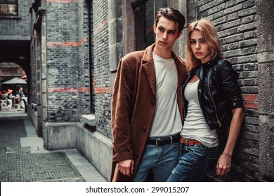 Young man and woman posing of the street with brick walls. Fashion vogue.