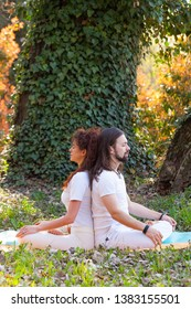 young man and woman practice partner yoga outdoor in wood summer day