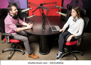 Young man and woman presenters in radio station hosting a live radio show