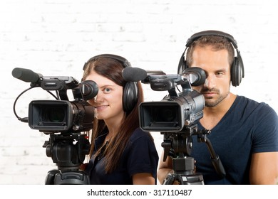young man and woman with professional video cameras