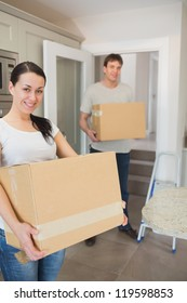 Young man and woman relocating and holding boxes in their hands