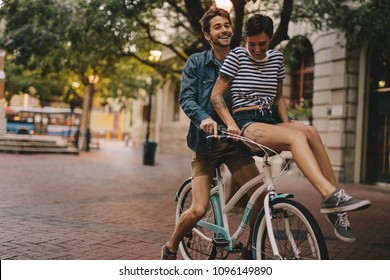 Young man and woman riding on a bicycle in the city. Happy couple on a bicycle in the city.