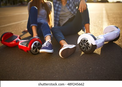 young man and woman riding on the Hoverboard in the park. content technologies. a new movement. Close Up of Dual Wheel Self Balancing Electric Skateboard Smart