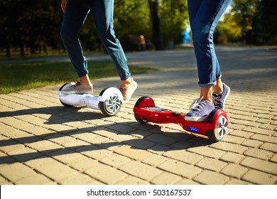 young man and woman riding on the Hoverboard in the park. content technologies. a new movement. Close Up of Dual Wheel Self Balancing Electric Skateboard Smart. on electrical scooter outdoors