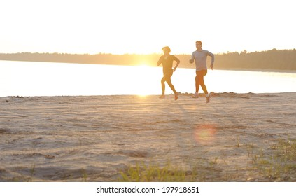 Young man and woman running along the waterfront in sunshine